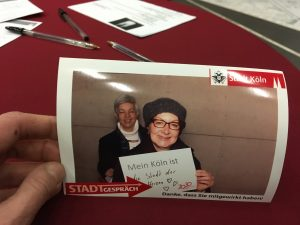 Auf dem Foto sind zwei Frauen zu sehen. Eine heißt Sabine Röltgen und hält ein Schild in der Hand mit dem Text: Mein Köln ist.... die Stadt der Herzen.